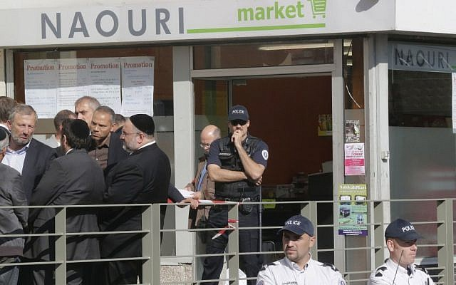 Police and members of the Jewish community stand in front of a kosher supermarket in Sarcelles, north of Paris, where a bomb exploded last month (photo credit: AP/Michel Euler)