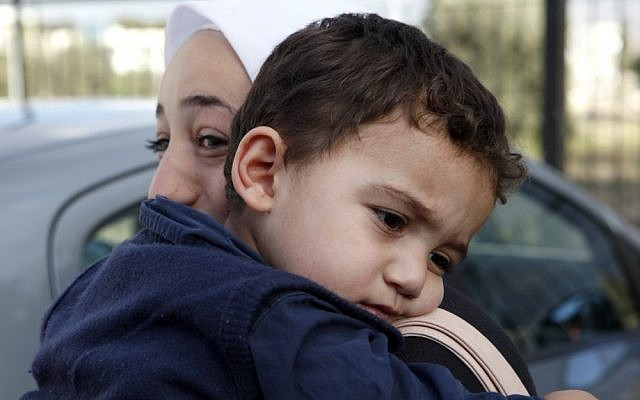 Bushr al-Tawashi, as he is carried by his mother Arin Al Dakkar, outside of a private Sigma TV station, in Nicosia, Cyprus, Friday. (photo credit: AP)