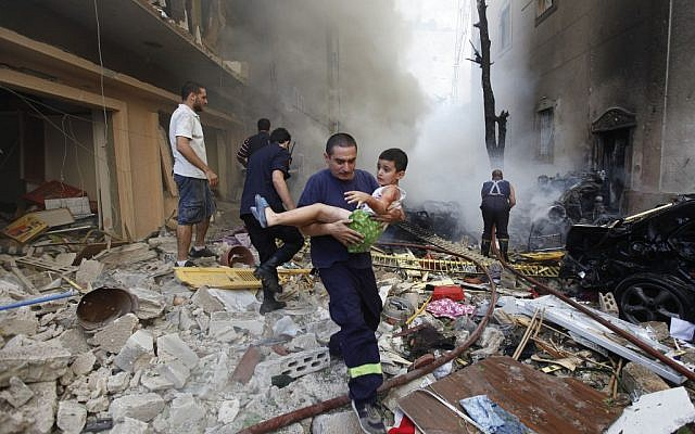 A Lebanese rescue man carries an injured boy at the scene of an explosion in the mostly Christian neighborhood of Achrafiyeh, Beirut, Lebanon, Friday Oct. 19, 2012 (photo credit: AP/Hussein Malla)