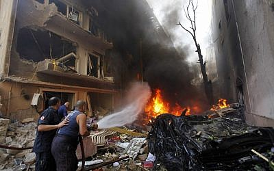 Lebanese firefighters extinguish burning cars at the scene of an explosion in the mostly Christian neighborhood of Achrafiyeh, Beirut, Lebanon, Friday Oct. 19 (photo credit: AP/Hussein Malla)