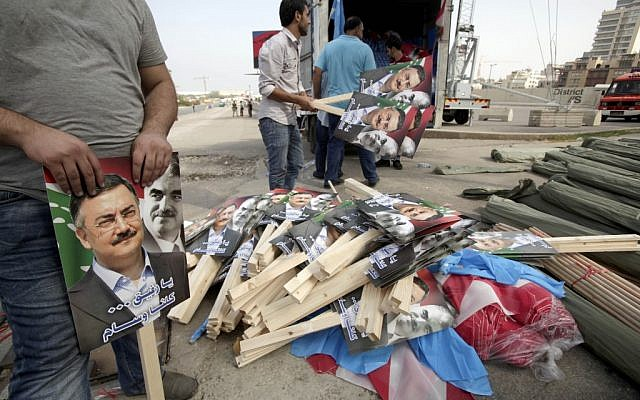 Volunteers distribute placards in Martyrs' Square before the funeral for the country's intelligence chief, Brig. Gen. Wissam al-Hassan in Beirut on Sunday. (photo credit: AP/Maya Alleruzzo)