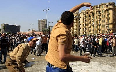 A protester throws a stone after scuffles broke out Friday between groups of several hundred protesters in Cairo's Tahrir square when chants against the new Islamist president angered some in the crowd. (photo credit: AP Photo/Khalil Hamra)