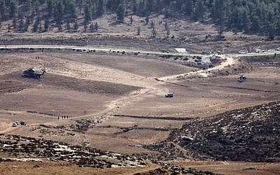 Israeli Army vehicles and helicopters are seen in an open area as they search for the remains of a drone in the Negev southern Israel, Saturday. (photo credit: AP)