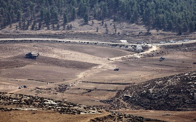 Army vehicles and helicopters are seen in an open area as they search for the remains of a drone in the Negev Saturday. (photo credit: AP/Yehuda Lachiani)