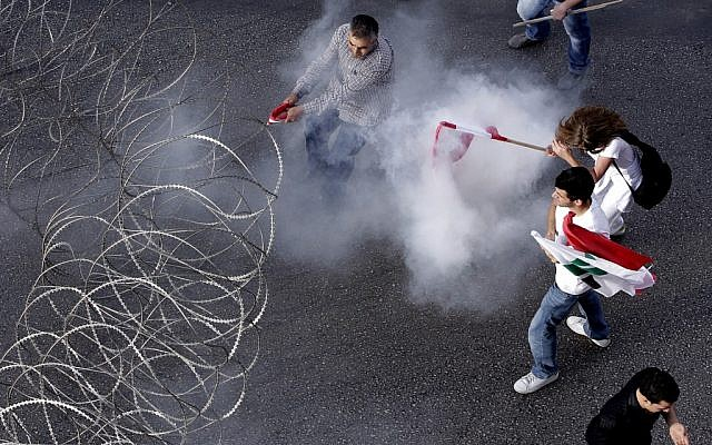 Lebanese protesters are enveloped in tear gas as they pull a barbed-wire barrier during clashes after the funeral of Brig. Gen. Wissam al-Hassan who was assassinated on Friday by a car bomb in Beirut, Lebanon, Sunday Oct. 21 (photo credit: AP/Hussein Malla)