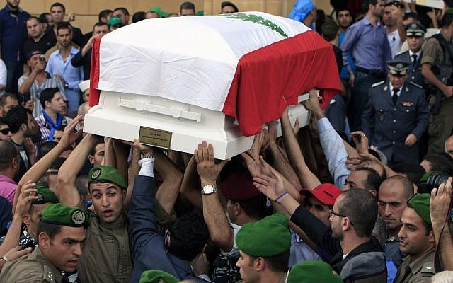 Lebanese honor guards carry coffins wrapped with Lebanese flags of Brig. Gen. Wissam al-Hassan and his bodyguard, Ahmad Sahyouni, who were assassinated on Friday by a car bomb, during their funeral procession at Martyrs' Square in Beirut, October 21, 2012 (photo credit: AP/Bilal Hussein)
