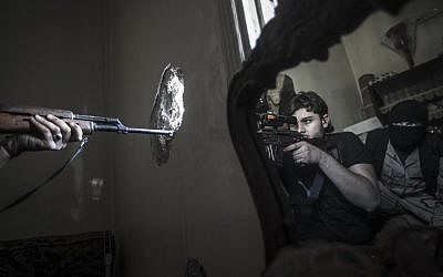 In this Monday, Oct. 29, 2012 photo, a rebel sniper aims at a Syrian army position, seen with another rebel fighter reflected in a mirror, in a residential building in the Jedida district of Aleppo, Syria (photo credit: AP Photo/Narciso Contreras)