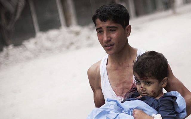 A Syrian youth holds a child wounded by Syrian Army shelling in Aleppo on Thursday (photo credit: AP/Manu Brabo)