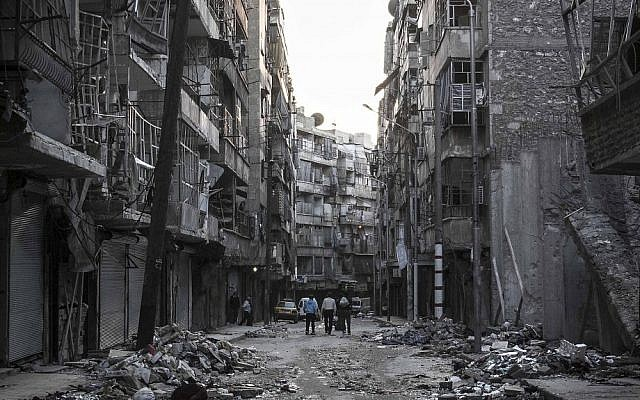 Syrians walk among the debris of buildings damaged by heavy shelling southeast of Aleppo on Saturday (photo credit: AP/Narciso Contreras)