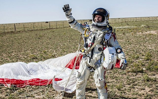Austria's new national hero, Felix Baumgartner, raises his arm in a triumphant salute -- not that other kind of salute -- after safely falling from roughly 24 miles above the surface of the Earth. (Photo credit: Balazs Gardi/AP/Red Bull Stratos)