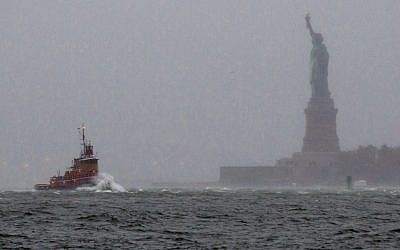 Waves crash over the bow of a tug boat as it passes near the Statue of Liberty in New York Monday, Oct. 29, 2012 as rough water as the result of Hurricane Sandy churned the waters of New York Harbor (photo credit: AP/Craig Ruttle)
