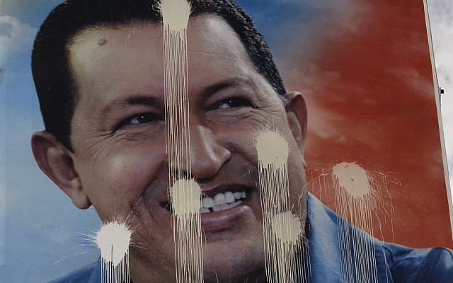 A defaced election campaign poster of Venezuela's President Hugo Chavez hangs in Caracas, Venezuela (photo credit: Fernando Llano/AP)