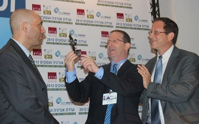 Shaul Tzemach, Directory General of the Ministry of Energy and Water, looks on as Dr. Amit Mor, Co-CEO of Eco Energy, presents Yosef Abramowitz, President of Arava Power Company, the 2012 Energy and Business Convention Person of the Year Award for the accomplishments of the Arava Power team in developing the solar power industry in Israel. (Photo credit: Hannah Schafer)