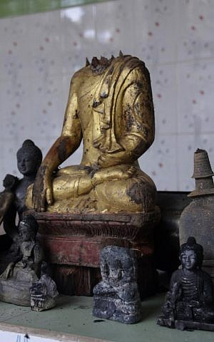 A Buddha statue stands amidst the ruins of a Buddhist temple that was torched Sunday by Muslims over an alleged derogatory photo of the Quran on Facebook. The temple is located in the coastal district of Cox's Bazar, Bangladesh. (photo credit: AP Photo)