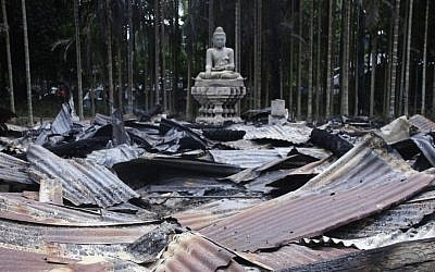 A Buddha statue stands amidst the ruins of a Buddhist temple that was torched Sunday by Muslims over a derogatory photo of the Quran on Facebook. The temple is located in the coastal district of Cox's Bazar, Bangladesh. (photo credit: AP Photo)
