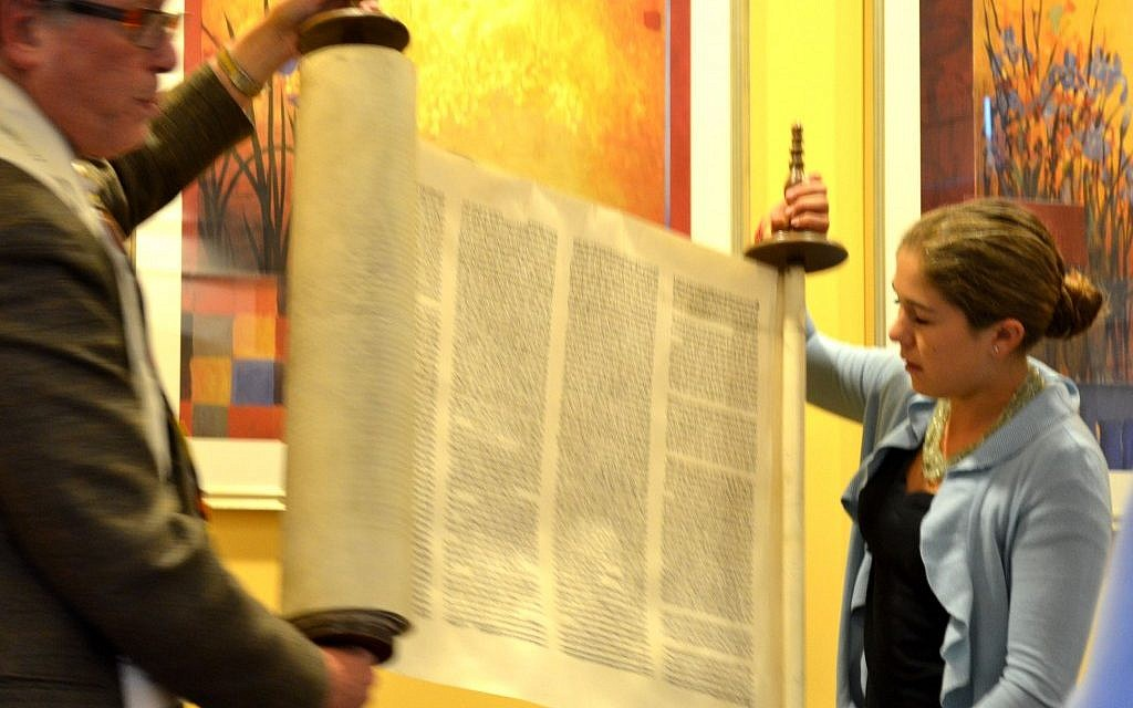 Charlotte Smith and Rabbi Jerry Levy dedicate the family Torah scroll rescued by her great-great-grandfather. (Julie Ann Kodmur via JTA)