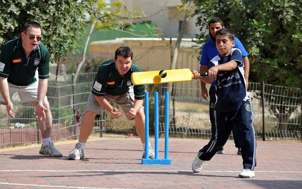 Nigel Adams, MP for Selby and Ainsty, left, and Guy Opperman, MP for Hexham, center, coaching a Bedouin cricketer in Hura (photo credit: David Katz/The Israel Project)