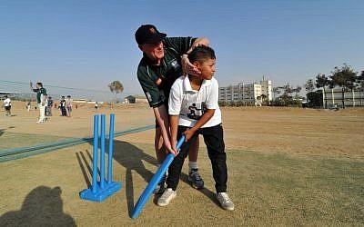 Legendary English spin bowler John Emburey coaching a young Palestinian cricketer in Beersheba (photo credit: David Katz/The Israel Project)