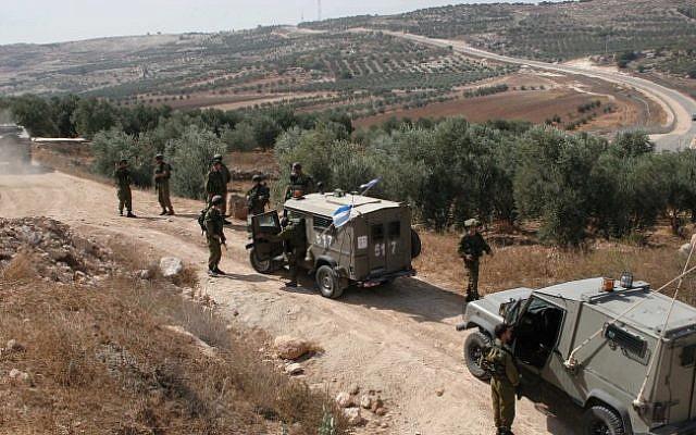 Israeli soldiers protect Palestinian olive pickers near Hebron in 2011 (Photo credit: Najeh Hashlamoun/Flash90)