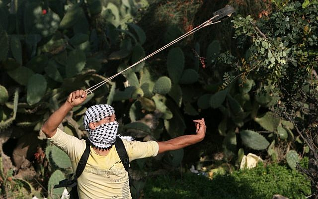 Illustrative photo of a  Palestinian youth hurling a stone in the West Bank city of Naalin in 2009 (photo credit: Miriam Alster/ flash90)
