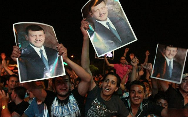 Jordanians celebrating the country's Independence Day in Amman wave posters of King Abdullah, June 1 (photo credit: Issam Rimawi/FLASH90)
