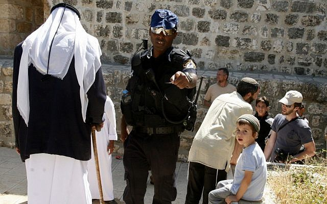Illustrative photo of an Israeli police officer with Muslims and Jews at the entrance to the Temple Mount in July 2012 (photo credit: Mahfouz Abu Turk/Flash90)