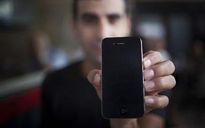 An illustrative photo of a man holding an iPhone (Yonatan Sindel/Flash90)