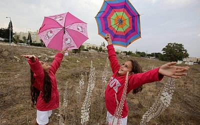 Israeli children running with umbrellas during the first rain of the year. (photo credit: Edi Israel/Flash90)