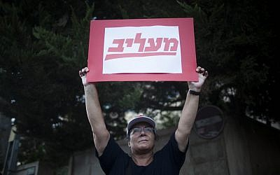 A Maariv newspaper worker protests outside the Prime Minister's Residence. The sign reads 'insulting' -- a play on words of the newspaper Maariv. (photo credit: Yonatan Sindel/Flash90)