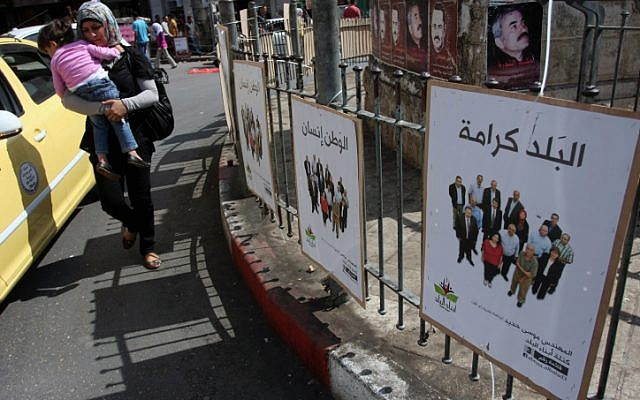 A Palestinian woman carries her baby past campaign posters in Ramallah on the first day of campaigning for local elections on October 6, 2012. (Issam Rimawi/Flash90)
