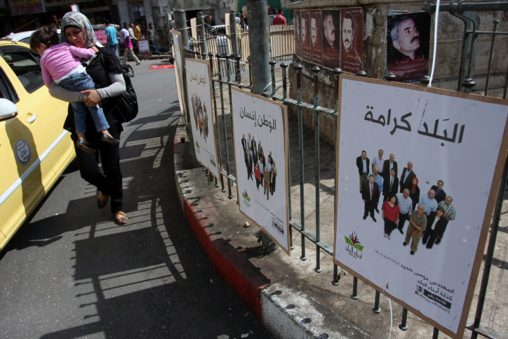 A Palestinian woman carries her baby past campaign posters in Ramallah on the first day of campaigning for local elections on October 6. (photo credit: Issam Rimawi/Flash90)