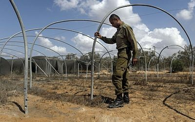 An Israeli army officer examines the area near the Israel-Gaza border, after it was hit by a mortar shell fired by Palestinian terrorists. (photo credit: Tsafrir Abayov/Flash90)