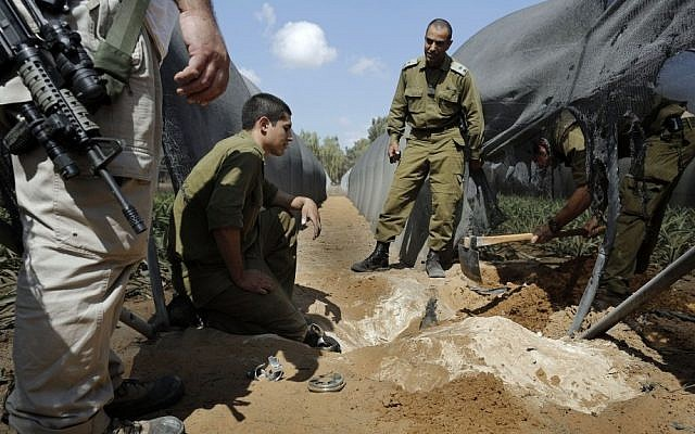 Members of the IDF's bomb squad search for a mortar shell in a greenhouse near Israel's border with the Gaza Strip after it was fired by Palestinian terrorists on Monday. Israeli forces and Palestinian terrorists exchanged fire on Monday in the most serious flare-up in months along the border with the Gaza Strip, officials said. (Tsafrir Abayov/Flash90).