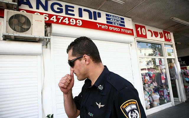 A police officer stands outside a money exchange kiosk in Herzliya whose operators were arrested under suspicion of money laundering on Wednesday, October 10, 2012 (Yehoshua Yosef/Flash90)