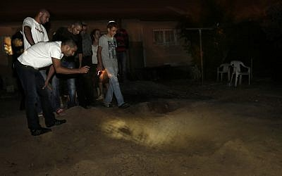 People inspecting a crater left in the backyard of a Netivot home after a Grad rocket crashed into it. (photo credit: Tsafrir Abayov/Flash90)