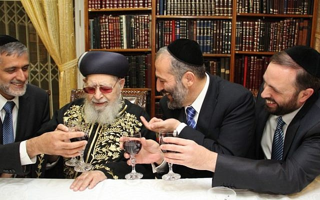 Shas founder Rabbi Ovadia Yosef (center) flanked on the left by MK Eli Yishai and on the right by MKs Aryeh Deri and Ariel Atias, at the rabbi's house in Jerusalem, October 2012. (photo credit: Shas/Flash90)
