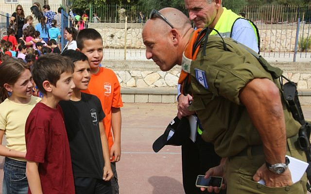 A Home Front Command officer talks with Israeli students during an earthquake drill at a Jerusalem school on October 21. Soldiers, emergency crews and civilians participated in the five-day civil defense drill, code-named Turning Point 6 on Sunday. (photo credit: Oren Nahshon/Flash90)