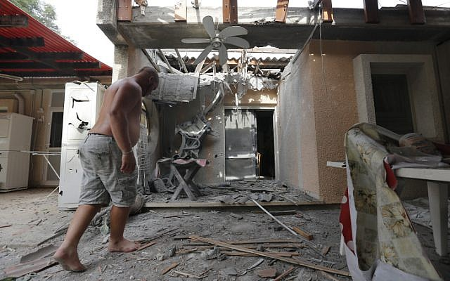 A man examines a damaged house after a rocket fired by Palestinian terrorists from the Gaza Strip hit a community in southern Israel, October 24, 2014 (photo credit: Tsafrir Abayov/Flash90)