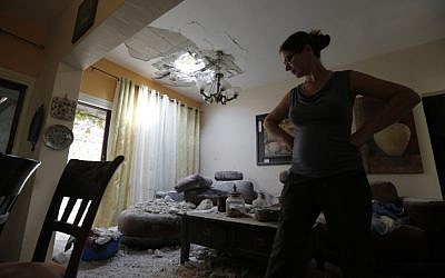 A woman examines a house in southern Israel damaged by a rocket fired by Palestinians in the Gaza Strip, Wednesday, October 24, 2012. (photo credit: Tsafrir Abayov/Flash90)