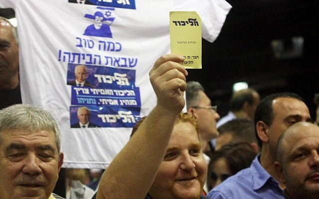 A member of Likud raises a yellow note in favor of the joint Likud-Yisrael Beytenu Knesset list, Monday at the Likud Central Committee meeting (photo credit: Roni Schutzer/Flash90)