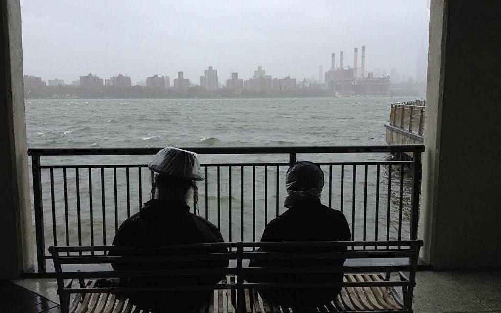 A Haredi couple awaits the arrival of Hurricane Sandy on Monday in Brooklyn. (Azi Paybarah via Twitter/JTA)