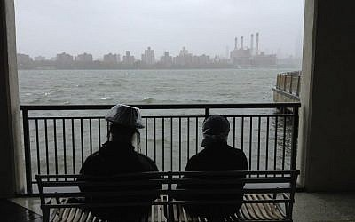 A Haredi couple awaits the arrival of Hurricane Sandy on Monday in Brooklyn. (Azi Paybarah via Twitter/JTA)