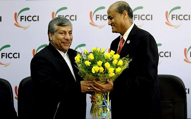 Federation of Indian Chambers of Commerce and Industry President, R. V. Kanoria, right, greets Iranian Energy Minister Majid Namjoo with a bouquet of flowers before an interactive business meeting in New Delhi, India on Wednesday. (photo credit: AP/Altaf Qadri)