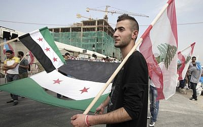 A man carries the Syrian revolutionary flag and a Lebanese national flag, as people gather in Martyrs' Square before the funeral for the country's intelligence chief, Brig. Gen. Wissam al-Hassan in Beirut, Lebanon, Sunday, October 21, 2012 (photo credit: AP Photo/Maya Alleruzzo)