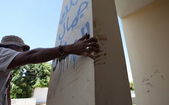 A Libyan man explains that the bloodstains on the column are from one of the American staff members who grabbed the edge of the column while he was evacuated, after an attack that killed four Americans, including Ambassador Chris Stevens on the night of Tuesday, Sept. 11, 2012, in Benghazi, Libya.  (photo credit: AP/Mohammad Hannon)