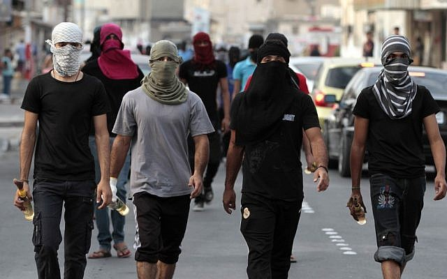 Illustrative photo of masked Bahraini anti-government protesters carrying Molotov cocktails ahead of a march in Manama in 2012. (photo credit: AP/Hasan Jamali)