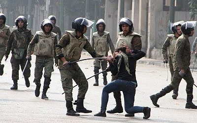 Egyptian army soldiers arrest a woman protester during clashes in Cairo's Tahrir Square on December 16, 2011 (photo credit: AP Photo/File)