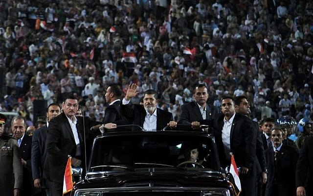 Egyptian President Mohammed Morsi waves to a Cairo crowd in October before making a speech on the national holiday that marks Egypt's 1973 war with Israel (photo credit: AP/Egyptian Presidency)