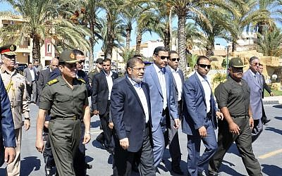 President Mohammed Morsi, center, walks with officials during a visit to el-Arish on Oct. 5. (photo credit: AP/Egyptian Presidency)