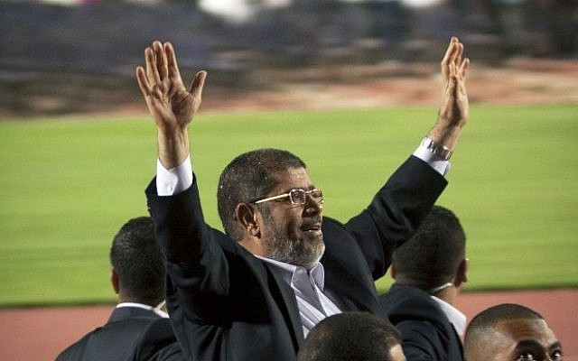 Egyptian President Mohammed Morsi waves to a crowd gathered at a Cairo stadium. (photo credit: AP)